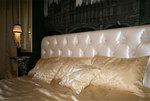 Изголовье кровати украшено каретной стяжкой